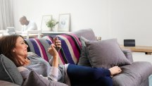 Woman on sofa using tablet with BT Smart Hub in the background