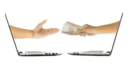 Two laptops with hands exchanging money