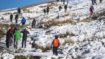 People walk over the snow covered mountain of Pen y fan, the highest peak in south Wales, situated in the Brecon Beacons National Park and standing at 886 metres above sea-level. (PA)