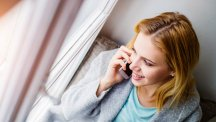 Woman using phone and smiling