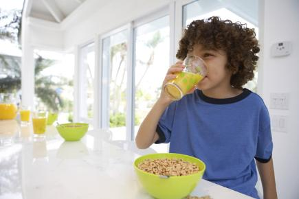 Young boy eating breakfast and drinking juice