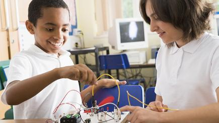 Young boy working on a circuit board