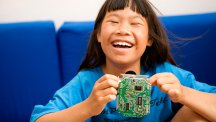 Young girl holding computer circuit board
