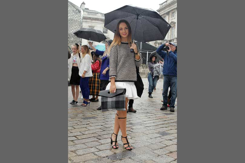 A white skirt is cosied up with a plaid clutch and geo print knit.