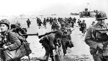 Allied troops wade ashore from their landing craft
