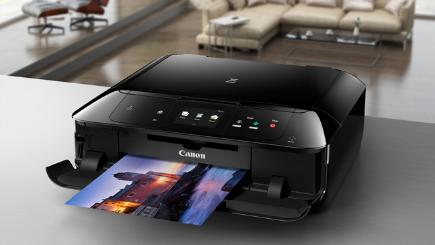 Black Canon printer on desk with print