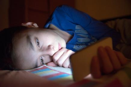 Boy lying on bed looking sadly at phone