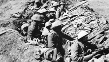 British infantrymen occupy a shallow trench in a ruined landscape before an advance during the Battle of the Somme.