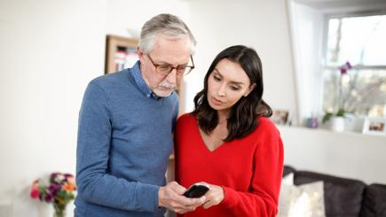Christine Lampard looking at phone with older man