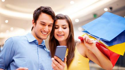 Woman and man looking at phone with shopping bags