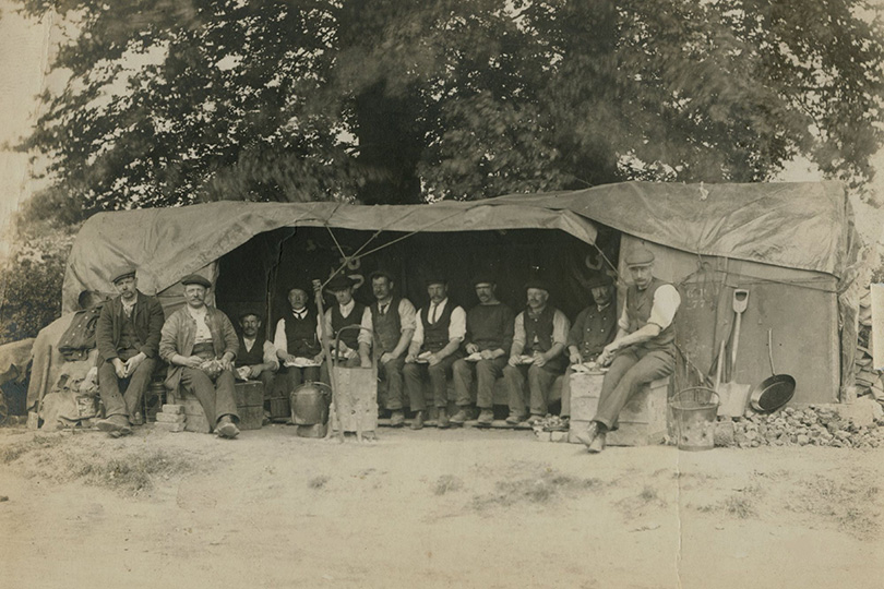 Cabling gang at lunch in large shelter tent, Uxbridge Road, London. c1910.