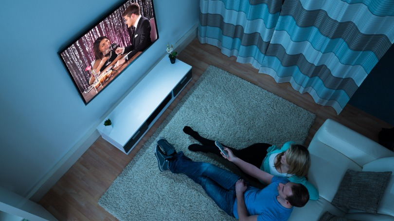 A couple watch a movie in a darkened room, sitting on the floor