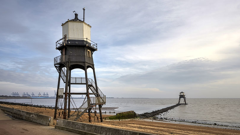 Dovercourt High and Low Lights (lighthouses), in Essex, with Felixstowe, Suffolk, in the background