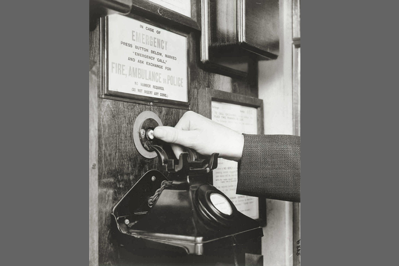 Emergency alarm button in a public telephone kiosk. 1935.