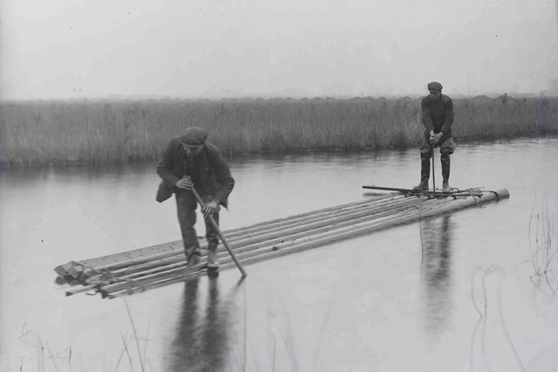 Engineers floating telegraph poles by water, Tilbury Marshes, Essex. 1941.
