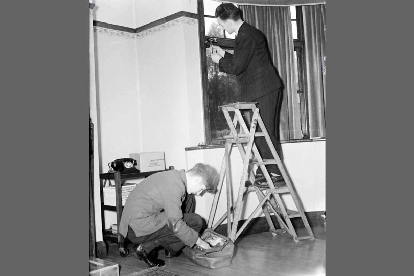 Engineers installing a telephone at a customer's premises. 1954.