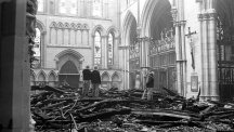 Firemen survey the fire damage to the South Transept of York Minster after the fire.