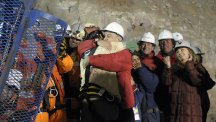 Florencio Avalos, the first miner to be rescued, left, is embraced by Chilean President Sebastian Pinera.