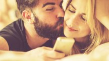 Couple kissing with phone sunlight