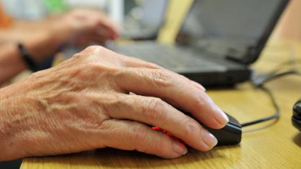 Hand using mouse by laptop