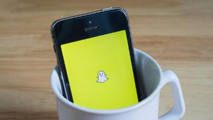 Snapchat on phone in cup