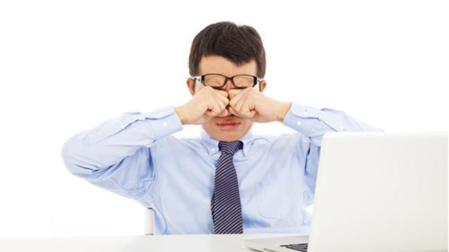 Man rubbing his eyes at laptop