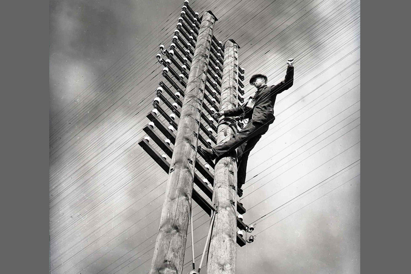 "Lineman working at the top of an""H"" telegraph pole. 1934."