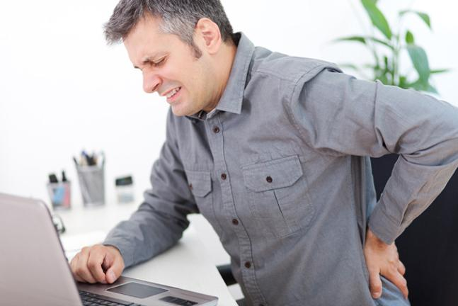 Man at computer looking pained rubbing back