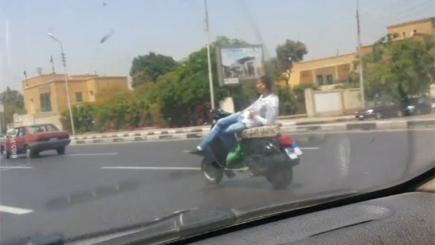 Screengrab of man reclining on his scooter as he drives it down a busy road in Cairo.  Photo credit: Newsflare