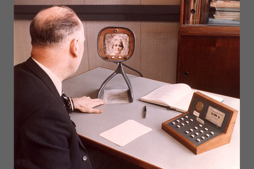 Man looking at the screen of a videophone. 1970.