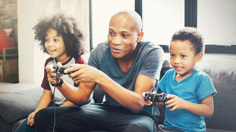 Man sat on sofa with two children playing console games