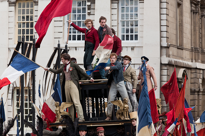 Marius Pontemercy and a group of students waving French flags in a rebellion