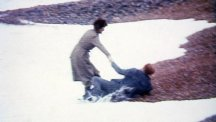 Neil Kinnock and wife Glenys are caught by the waves on Brighton beach.