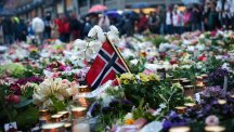 Norwegian flags, flowers and candles commemorating the victims of the attacks are seen at the ground in front of the Domkirke church in central Oslo.