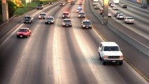 OJ Simpson's Ford Bronco leads a phalanx of LAPD cars around the Interstate road.