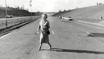 Prime Minister Margaret Thatcher poses on an empty M25 before its official opening.