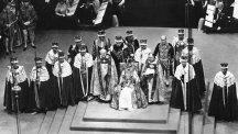 Queen Elizabeth II sits on the throne in Westminster Abbey surrounded by peers and churchmen.