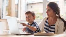 Woman and boy looking at laptop in kitchen