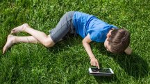 Boy lying on grass using tablet