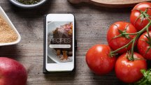 Phone on table with recipes next to tomatoes