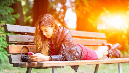 Girl on bench looking at phone