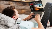Man on bed watching TV on laptop