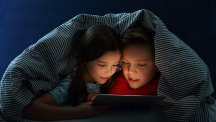 Two kids under covers looking at tablet